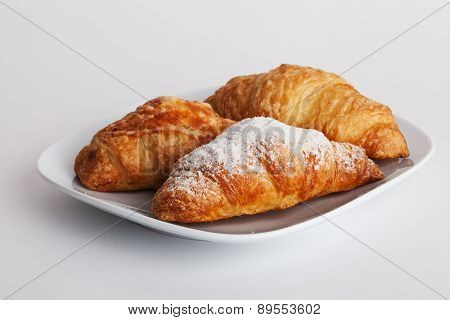 Three croissant on a plate white background