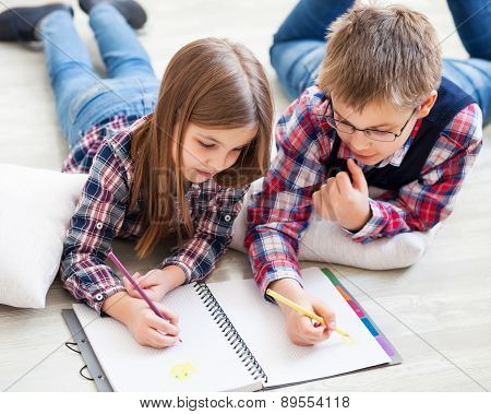 Two Little Kids Drawing With Crayons