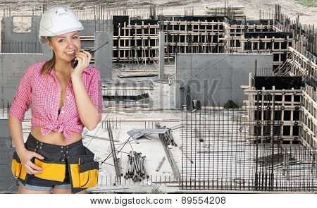 Young woman in hard hat holding walkie talkie