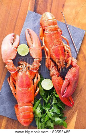 Cooked Lobsters On A Table With Lime And Parsley