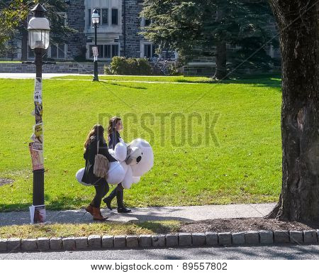 Campus Of Princeton University - Two Students Carrying Big White Toy