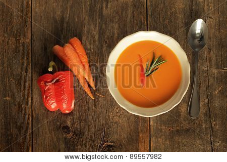 Carrot and grilled pepper soup on a wooden background