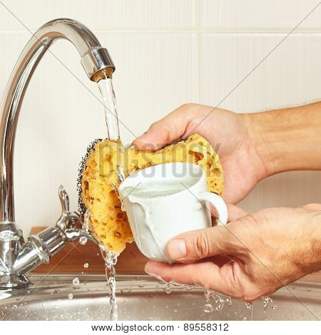 Hands wash the cup under running water in kitchen