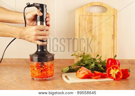 Hands cooks chopped red pepper in blender