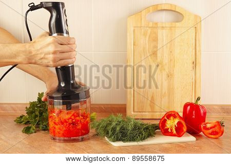 Hands cooks are going to mix red pepper and tomato in blender