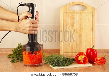 Hands cooks mixed red pepper and tomato in blender