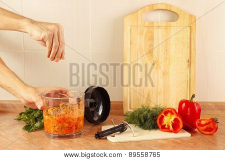 Hands of chef salt cooked vegetable salsa in blender