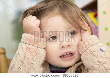 Little Girl Whose Face And Sweater Is Smudged With Paint