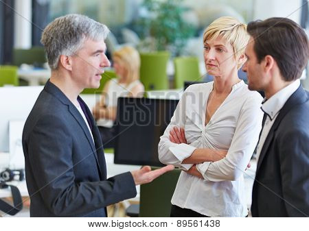 Business team communication in the office with elderly businessman talking