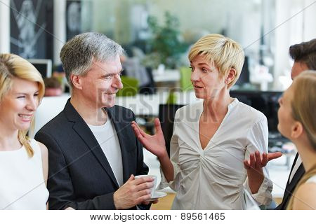 Woman in office telling joke to her team and her colleagues laughing