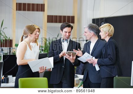 Business men and women in office working with tablet PC