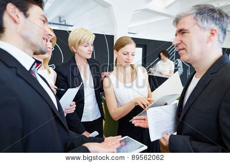 Team of business people in office talking to each other