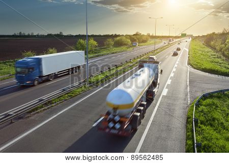Two Trucks On The Highway At Sunset In Motion