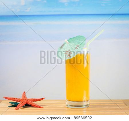 Glass Of Orange Juice On The Sea And Sandy Beach Near Starfish