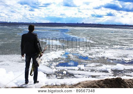 The guy with the guitar, stands on an ice floe in the sea