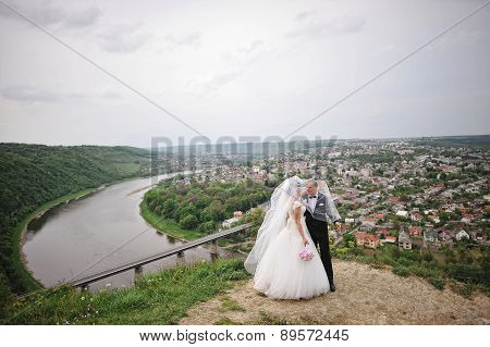 Wedding Couple Stay On A Hilltop Near The River And Bridge