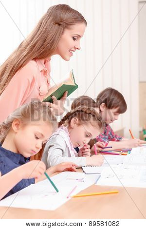 Teacher checking work of pupils