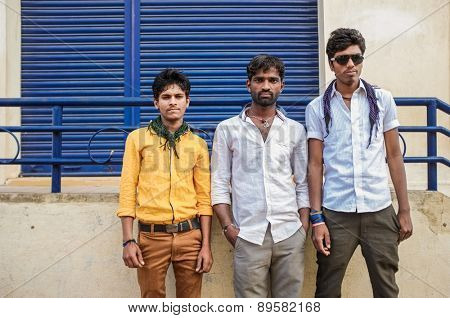 KAMALAPURAM, INDIA - 02 FEBRUARY 2015: Three indian youngsters standing on a marketplace close to Hampi