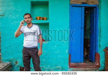 KAMALAPURAM, INDIA - 02 FEBRUARY 2015: Indian man talking on mobile phone outside his home
