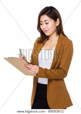 Asian businesswoman write on clipboard