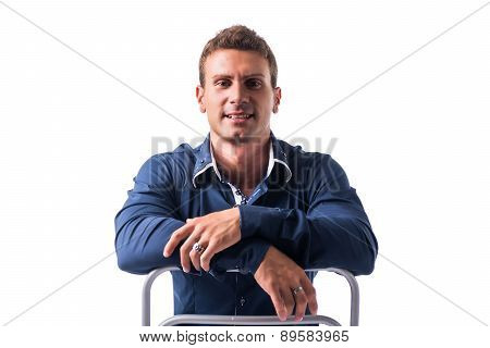 Smiling young man sitting on chair backwards