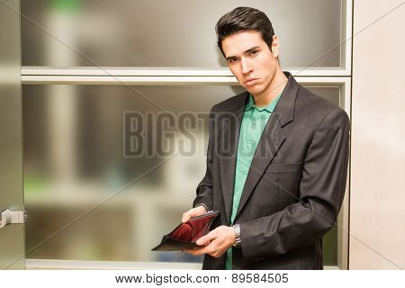Sad looking young man showing empty wallet