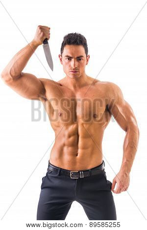 Handsome power athletic guy posing with knife