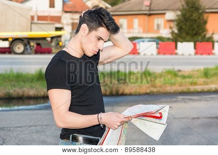 Young man searching for a location from printed map