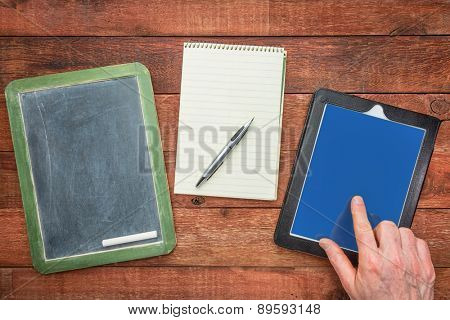 slate blackboard, with chalk, notepad with a pen and digital tablet with a finger - generations of making notes concept