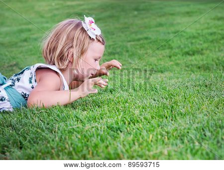Little Beautiful Girl  Lies On The Green Grass Outdoors In Summer Garden.