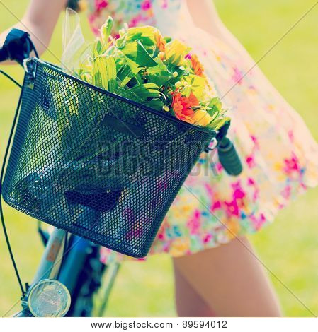 Girl in color short dress stands near bike with basket and flower bouquet. Toned Photo