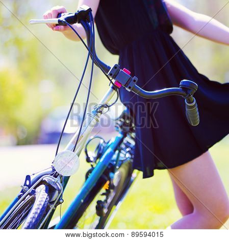 Girl in color short dress stands near bike with basket and flower bouquet