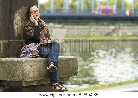 Young woman with laptop talking on the phone while sitting on the waterfront of beautiful old town.
