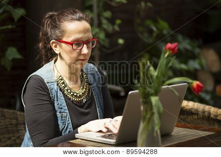 Female freelancer with a laptop in a summer cafe.