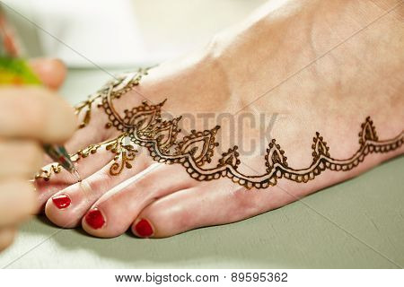 Mehendi. Master applying henna on model's leg