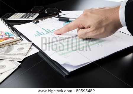 Businessman Point To  Business And Financial Report.