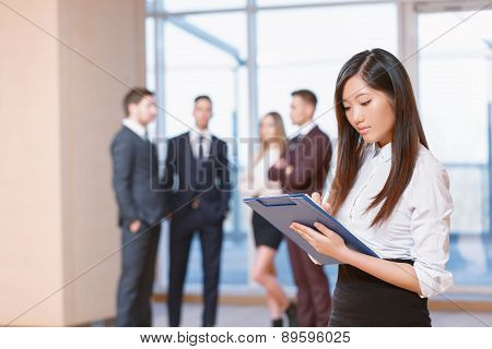 Asian young business woman standing in front of her co-workers