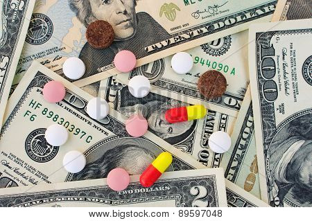 Different medical pills on the background of dollars