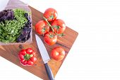 pic of leafy  - Preparing a healthy leafy green salad with farm fresh sweet bell pepper tomatoes and assorted lettuce cultivars on a wooden chopping board with a knife view from above on white with copyspace - JPG