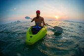 stock photo of kayak  - Young lady paddling the kayak in the open calm sea at sunset - JPG