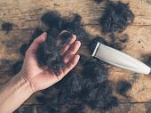 stock photo of hair cutting  - A male hand is holding some cut hair by a wooden table with a hair clipper - JPG