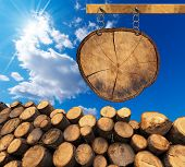 stock photo of cutting trees  - Trunks of trees cut and stacked and empty wooden sign a section of tree trunk hanging with metal chain on a wooden pole on blue sky with clouds and sun rays - JPG