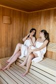 image of sauna woman  - Young women relaxing on the bench in sauna - JPG