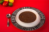 stock photo of jalapeno  - Bowl of traditional Hispanic black beans and jalapeno soup in High contrast red white and black setting with Aztec theme - JPG