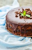 pic of cheesecake  - chocolate cheesecake with chocolate glaze on white wood background - JPG