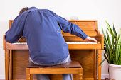 pic of stool  - Enthusiastic man playing the piano with gusto stretching to either end of the keyboard view from behind of him sitting on the stool leaning forwards - JPG