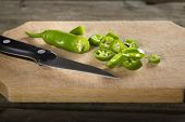 stock photo of chillies  - Chopped Fresh green chilli peppers On A cutting Wooden Board - JPG