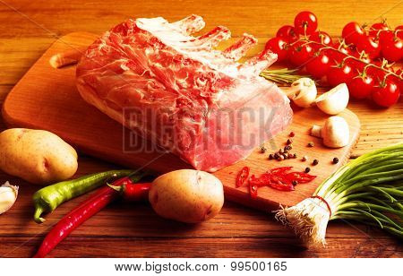 Raw Steak with vegetables on wooden board.Filtered image: warm cross processed vintage effect.