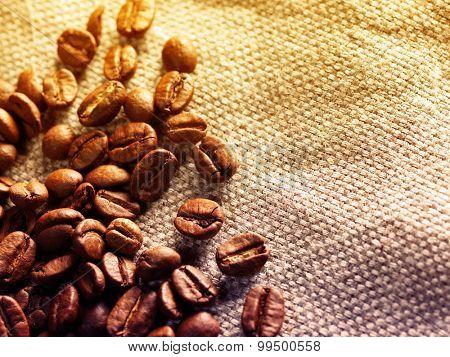 Coffee beans on burlap sack. Filtered image: vintage effect.