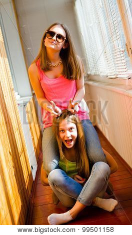 Two funny pretty teenage girls in sunglasses kidding having fun